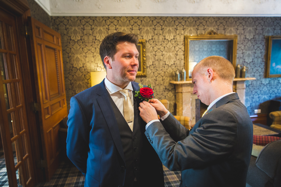 Winter wedding in Glasgow, Scotland. Groom getting buttonhole added.
