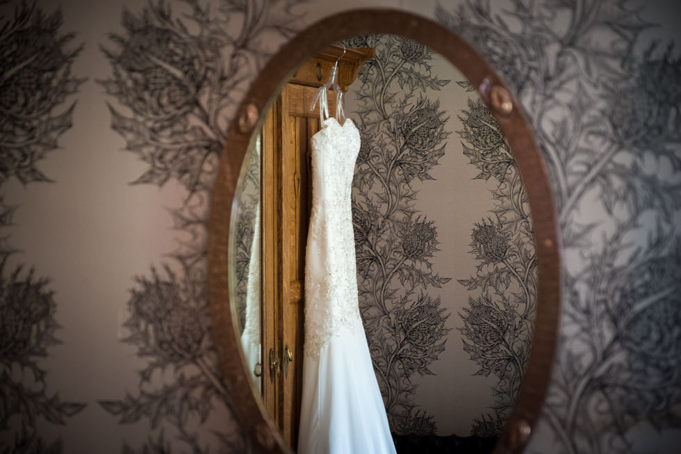 Lodge on Loch Goil Wedding. Reflection of wedding dress with Timorous Beasties wallpaper at the Lodge on Loch Goil