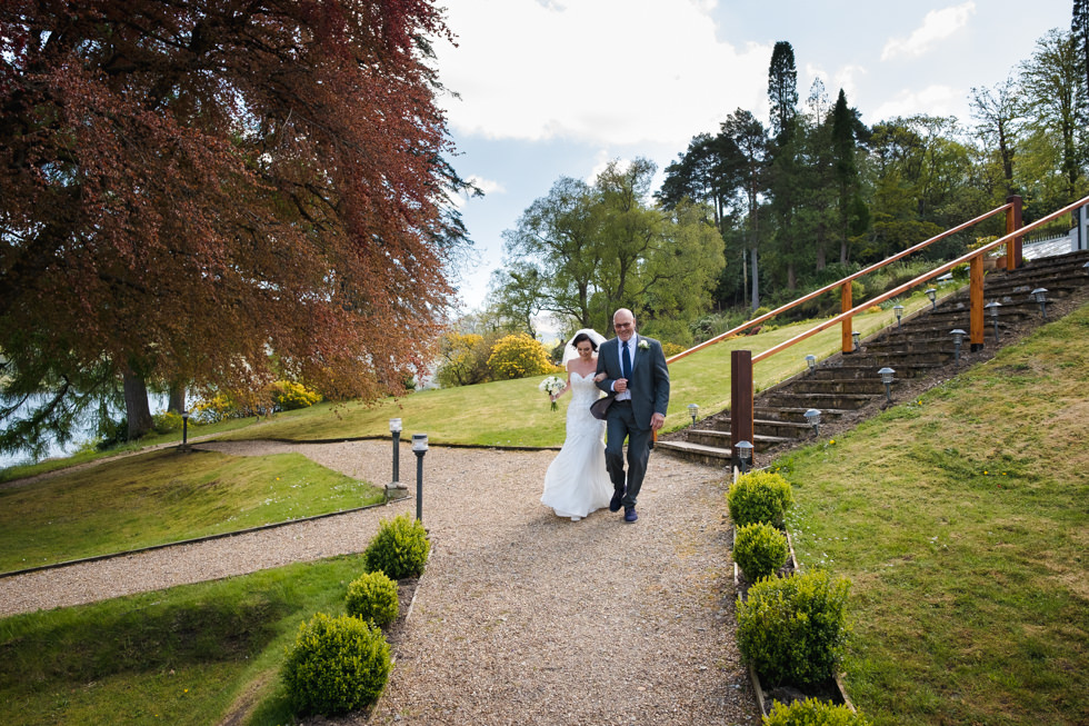 Lodge on Loch Goil Wedding, Bride and her father walking to the wedding ceremony at the Lodge on Loch Goil.