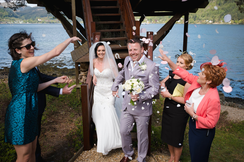 Lodge on Loch Goil Wedding. Newlyweds showered in confetti at the bottom of the steps to the treehouse.