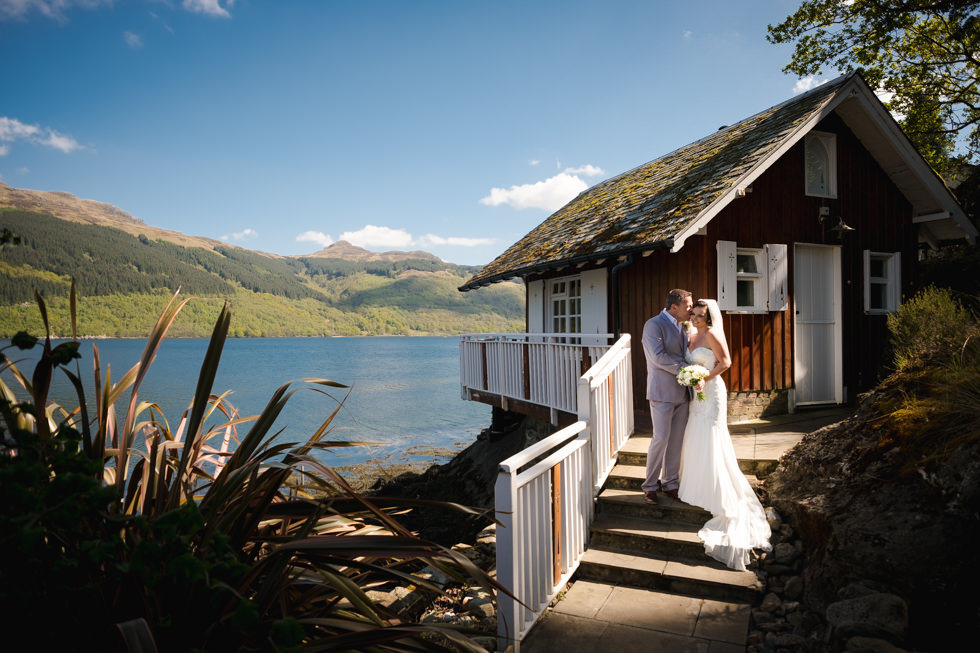 Lodge on Loch Goil Wedding. Bride and groom next to the treehouse at the Lodge on Loch Goil with a blue sky on their wedding day.