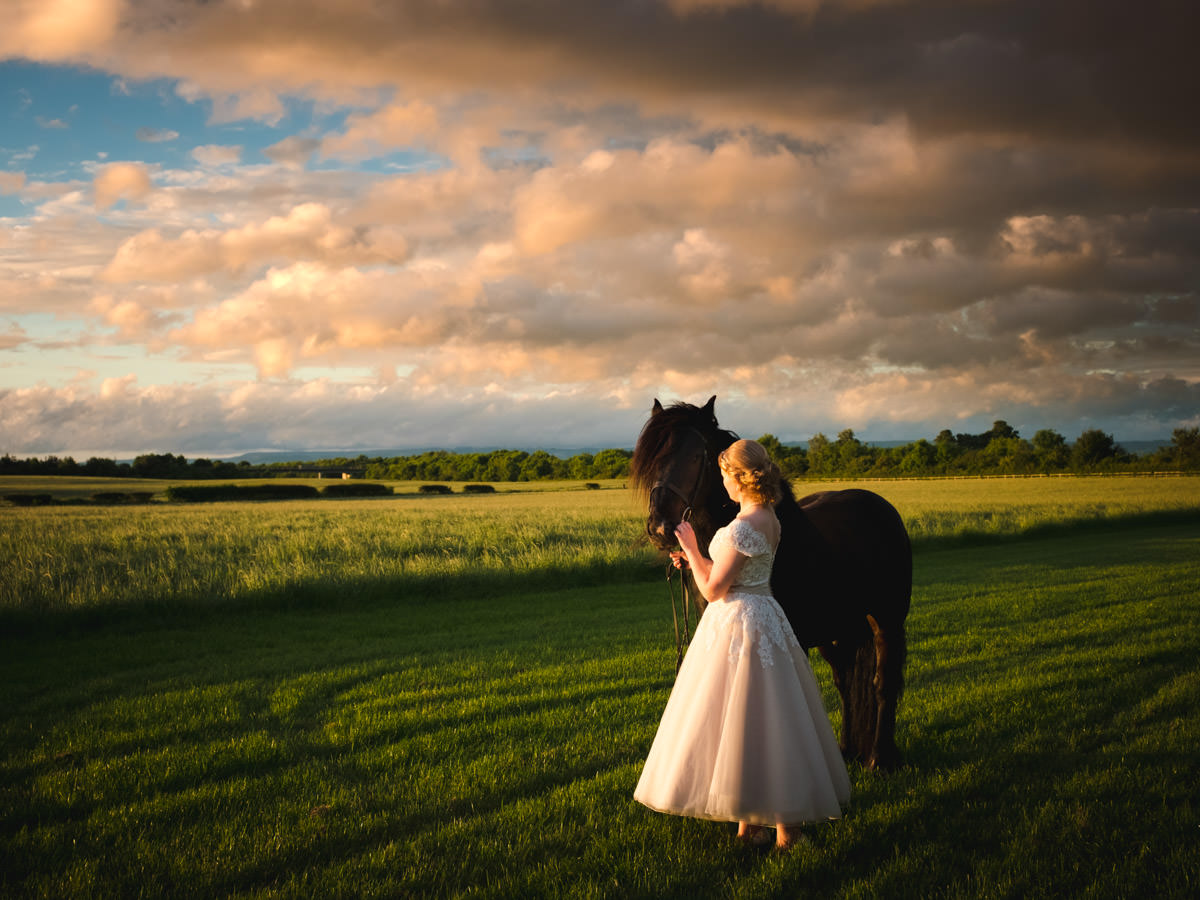 Yorkshire Wedding. Bride with her horse in a field at sunset.