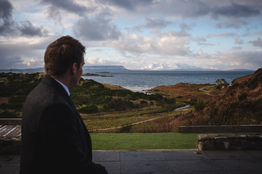 Winter Elopement Arisaig - groom looking out from Morar to isle of Rum