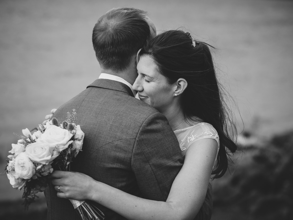 Black and white photograph of a bride and groom cuddling