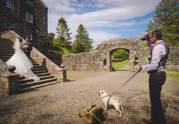 Trevor Wilson photographing a bride and groom whilst holding a dog.