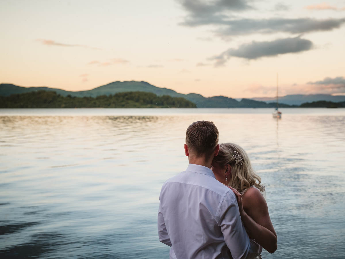 Bride and groom looking out over Loch Lomond in Scotland
